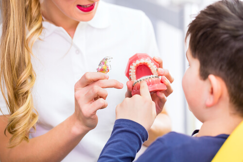 dentist explains the different types of braces to child