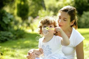 Mother-and-daughter-playing-with-soap-bubbles