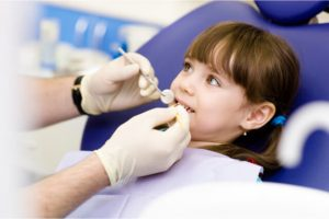 The young girl behaves quietly while the dentist performs the procedure.