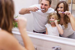 The parents teach their daughter to brush her teeth.