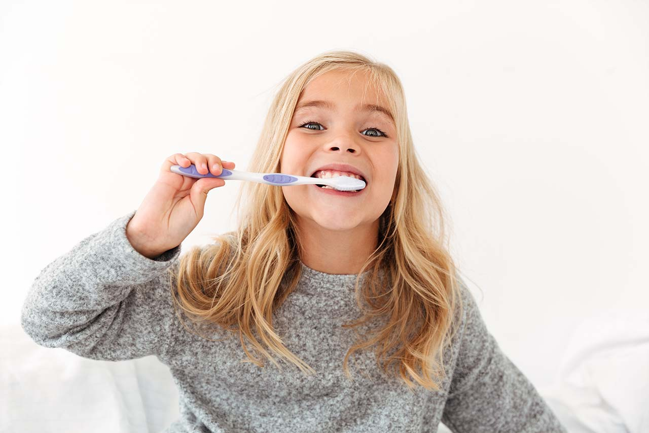 The young child brushes her teeth regularly.