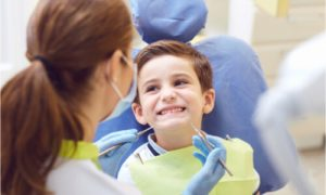 The dentist checks the child's teeth and mouth.