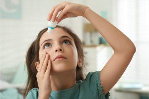 girl using eye drops